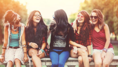 Teenage girls smiling and sitting on a bench outdoors in the summer